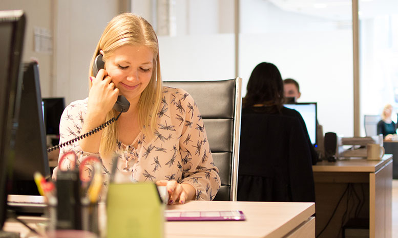 staff member at desk on phone